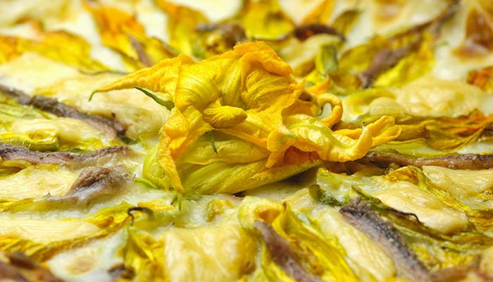Pizza en bandeja con flores de calabacín, anchoas y burrata